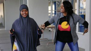 Hodman Hassan shares a laugh with theater artist Monique Gaffney at Crawford High. (Howard Lipin / San Diego Union-Tribune)